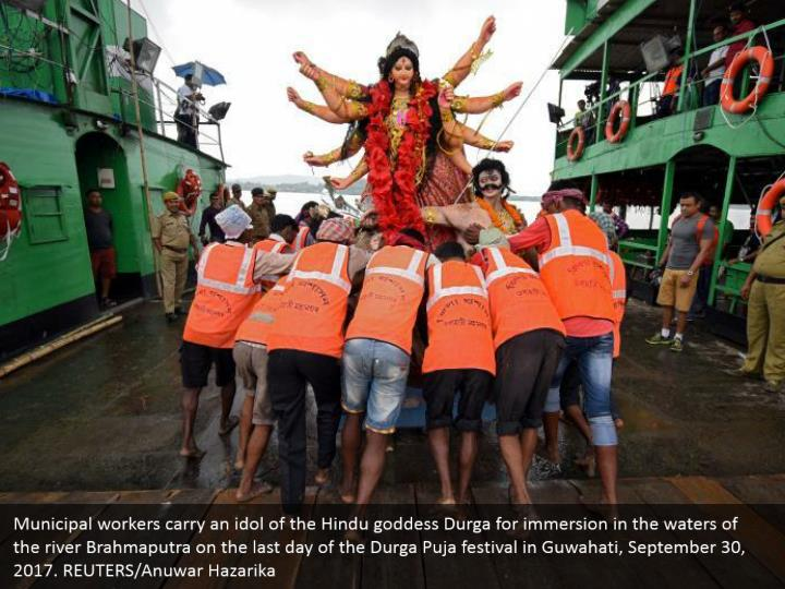 Municipal workers carry an idol of the Hindu goddess Durga for immersion in the waters of the river Brahmaputra on the last day of the Durga Puja festival in Guwahati, September 30, 2017. REUTERS/Anuwar Hazarika