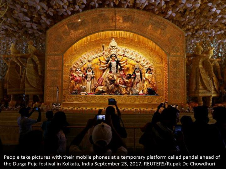 People take pictures with their mobile phones at a temporary platform called pandal ahead of the Durga Puja festival in Kolkata, India September 23, 2017. REUTERS/Rupak De Chowdhuri