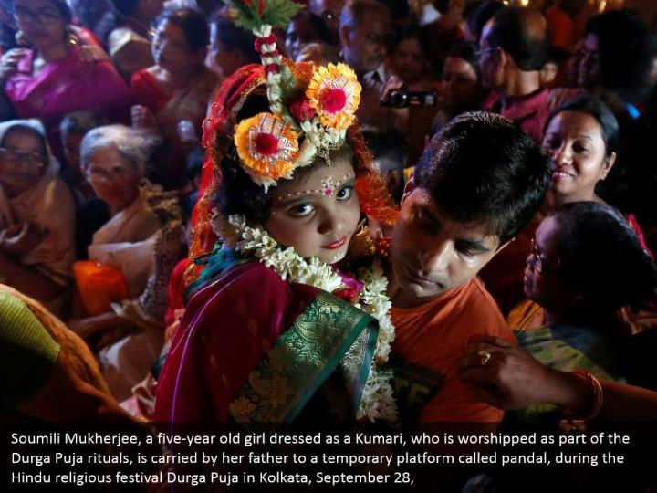 Soumili Mukherjee, a five-year old girl dressed as a Kumari, who is worshipped as part of the Durga Puja rituals, is carried by her father to a temporary platform called pandal, during the Hindu religious festival Durga Puja in Kolkata, September 28,