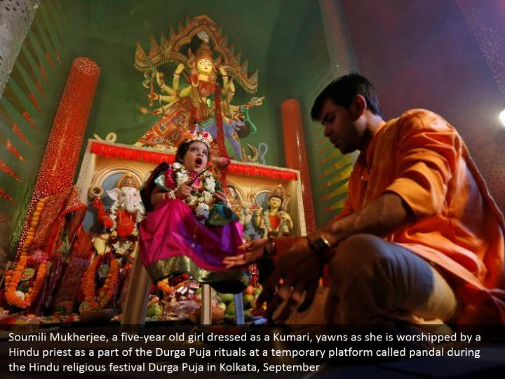 Soumili Mukherjee, a five-year old girl dressed as a Kumari, yawns as she is worshipped by a Hindu priest as a part of the Durga Puja rituals at a temporary platform called pandal during the Hindu religious festival Durga Puja in Kolkata, September