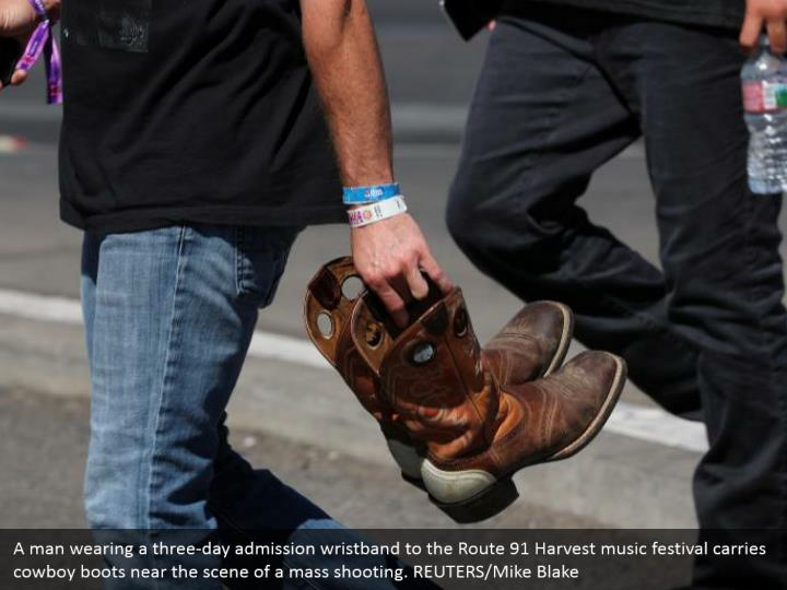A man wearing a three-day admission wristband to the Route 91 Harvest music festival carries cowboy boots near the scene of a mass shooting. REUTERS/Mike Blake