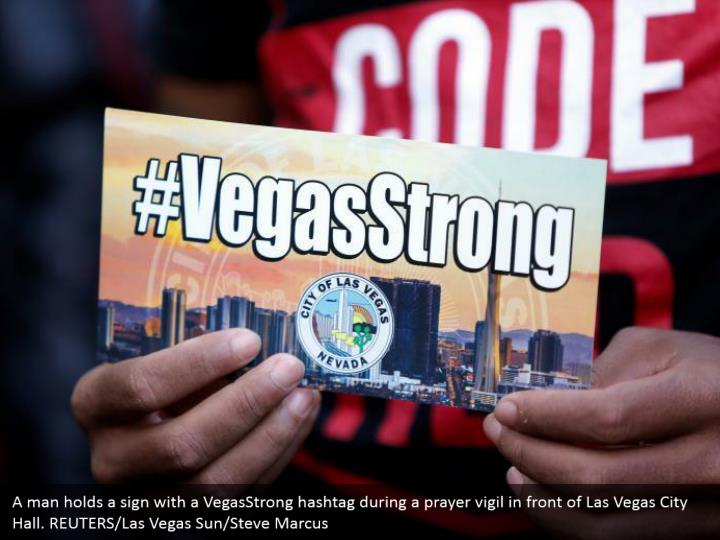 A man holds a sign with a VegasStrong hashtag during a prayer vigil in front of Las Vegas City Hall. REUTERS/Las Vegas Sun/Steve Marcus