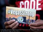 a man holds a sign with a vegasstrong hashtag