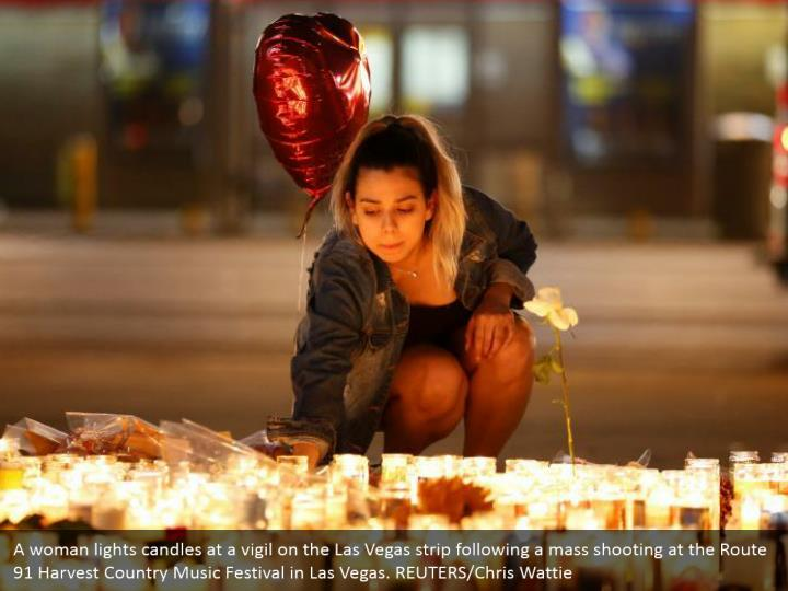 A woman lights candles at a vigil on the Las Vegas strip following a mass shooting at the Route 91 Harvest Country Music Festival in Las Vegas. REUTERS/Chris Wattie