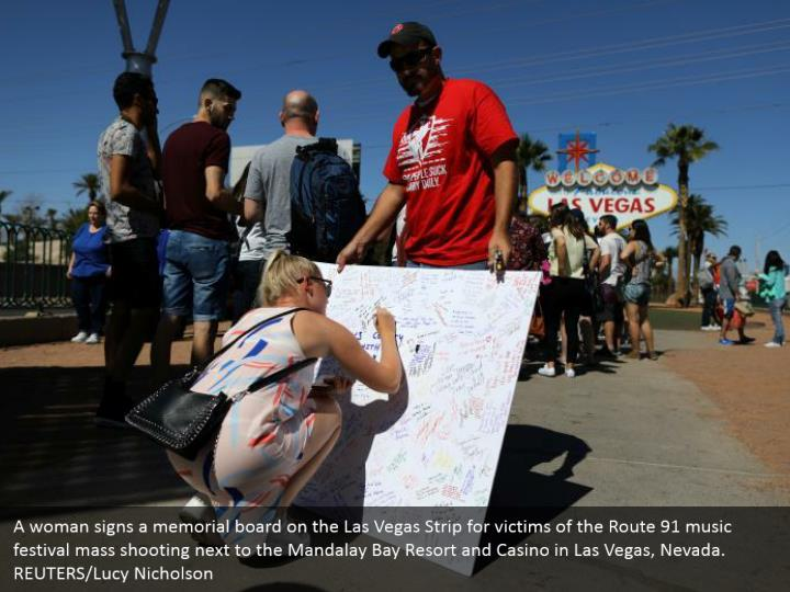 A woman signs a memorial board on the Las Vegas Strip for victims of the Route 91 music festival mass shooting next to the Mandalay Bay Resort and Casino in Las Vegas, Nevada. REUTERS/Lucy Nicholson