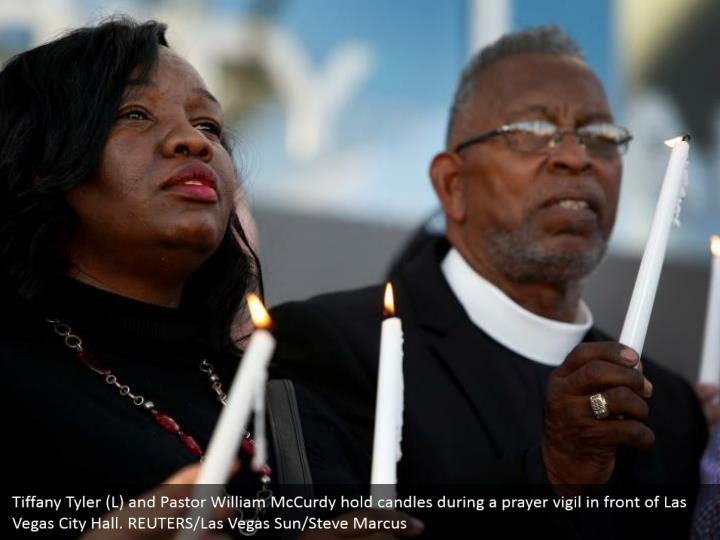 Tiffany Tyler (L) and Pastor William McCurdy hold candles during a prayer vigil in front of Las Vegas City Hall. REUTERS/Las Vegas Sun/Steve Marcus