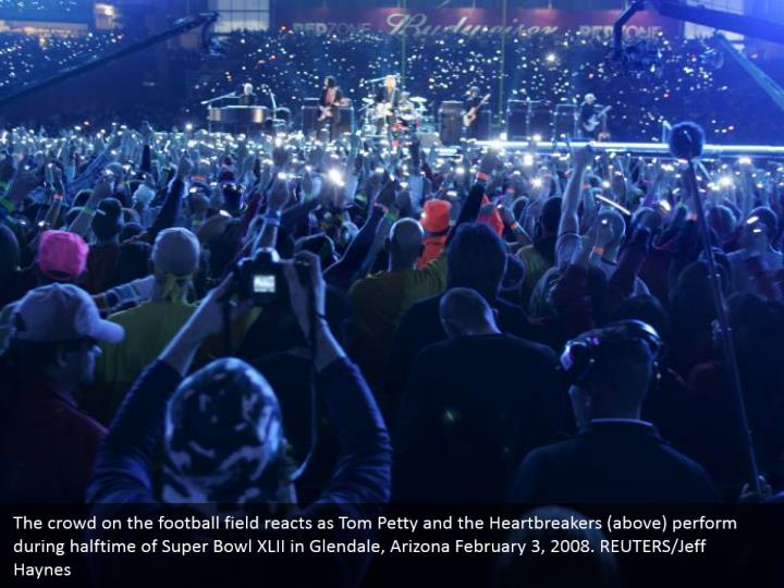 The crowd on the football field reacts as Tom Petty and the Heartbreakers (above) perform during halftime of Super Bowl XLII in Glendale, Arizona February 3, 2008. REUTERS/Jeff Haynes