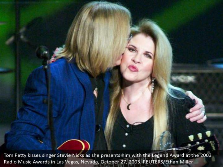 Tom Petty kisses singer Stevie Nicks as she presents him with the Legend Award at the 2003 Radio Music Awards in Las Vegas, Nevada, October 27, 2003. REUTERS/Ethan Miller