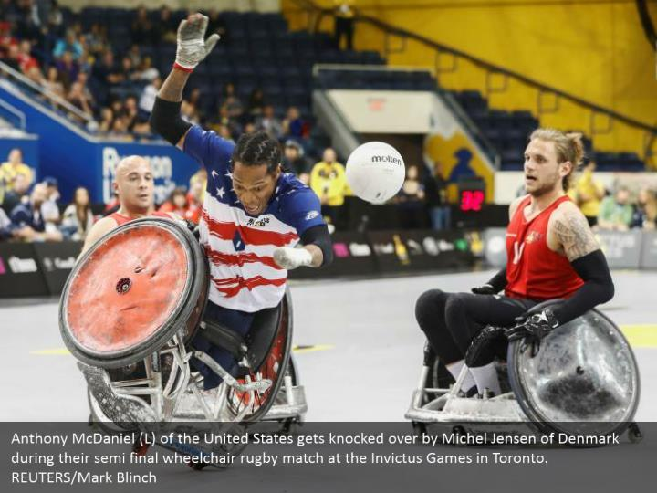 Anthony McDaniel (L) of the United States gets knocked over by Michel Jensen of Denmark during their semi final wheelchair rugby match at the Invictus Games in Toronto. REUTERS/Mark Blinch