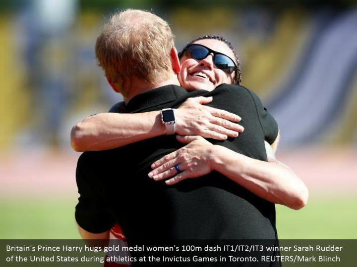 Britain's Prince Harry hugs gold medal women's 100m dash IT1/IT2/IT3 winner Sarah Rudder of the United States during athletics at the Invictus Games in Toronto. REUTERS/Mark Blinch