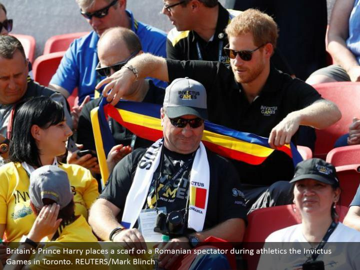 Britain's Prince Harry places a scarf on a Romanian spectator during athletics the Invictus Games in Toronto. REUTERS/Mark Blinch