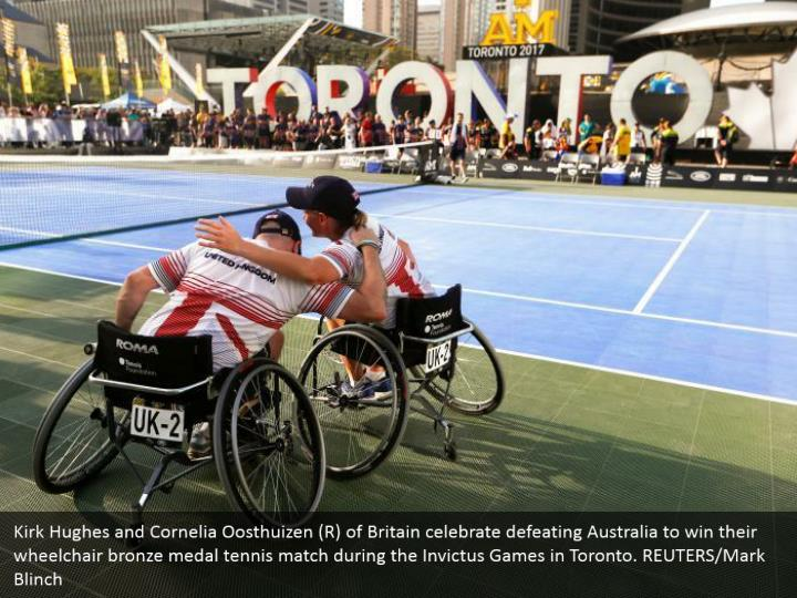 Kirk Hughes and Cornelia Oosthuizen (R) of Britain celebrate defeating Australia to win their wheelchair bronze medal tennis match during the Invictus Games in Toronto. REUTERS/Mark Blinch