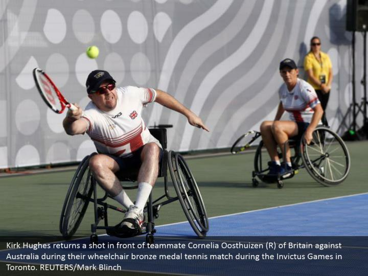 Kirk Hughes returns a shot in front of teammate Cornelia Oosthuizen (R) of Britain against Australia during their wheelchair bronze medal tennis match during the Invictus Games in Toronto. REUTERS/Mark Blinch