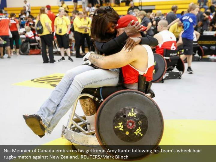 Nic Meunier of Canada embraces his girlfriend Amy Kante following his team's wheelchair rugby match against New Zealand. REUTERS/Mark Blinch