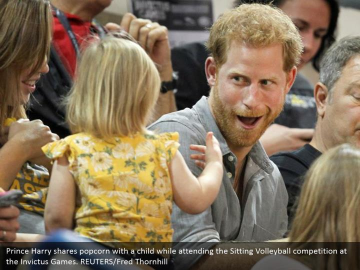 Prince Harry shares popcorn with a child while attending the Sitting Volleyball competition at the Invictus Games. REUTERS/Fred Thornhill