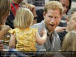 prince harry shares popcorn with a child while
