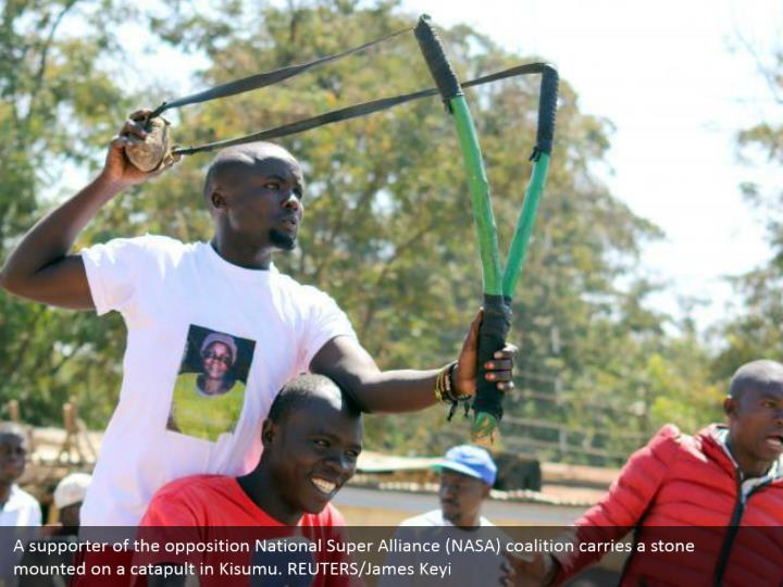 A supporter of the opposition National Super Alliance (NASA) coalition carries a stone mounted on a catapult in Kisumu. REUTERS/James Keyi