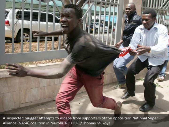 A suspected mugger attempts to escape from supporters of the opposition National Super Alliance (NASA) coalition in Nairobi. REUTERS/Thomas Mukoya