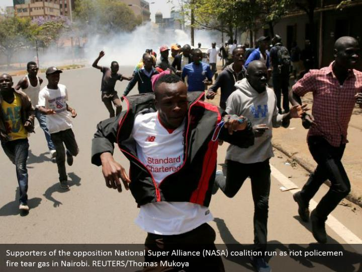 Supporters of the opposition National Super Alliance (NASA) coalition run as riot policemen fire tear gas in Nairobi. REUTERS/Thomas Mukoya