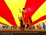 people walk under a huge catalan flag during