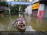 a woman paddles a boat past a school gate