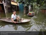 residents paddle boats in a flooded village 1