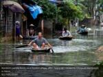 residents paddle boats in a flooded village after