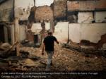 a man walks through burned houses following