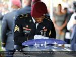 an honor guard member touches an american flag