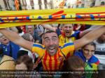 a man displays a scarf featuring an estelada