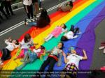 children play on a giant rainbow flag as they