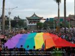 participants hold a giant rainbow flag as they