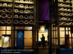 a visitor stands near torah scrolls on display