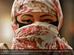 a woman walks with her face covered with a scarf