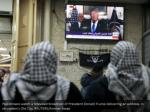 palestinians watch a televised broadcast