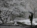 a man takes a photo in central park as the snow