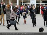 a racegoer chases her hat before the racing