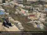 a kurdish man and woman sit on a mountain as they