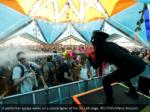 a performer sprays water on a concertgoer