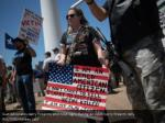 gun advocates carry firearms and hold signs