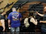 gun enthusiasts inspect rifles displayed