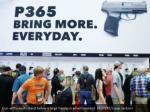 gun enthusiasts stand below a large handgun