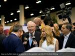 warren buffett talks to a reporter in the exhibit