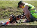 an instructor teaches a boy to shoot