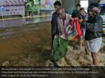 rescue workers help people to cross a flooded