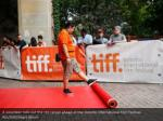 a volunteer rolls out the red carpet ahead