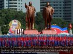 people carry flags in front of statues of north