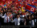 people wave plastic flowers and flags during