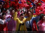 people wave plastic flowers during a military