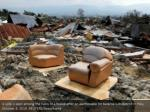 a sofa is seen among the ruins of a house after